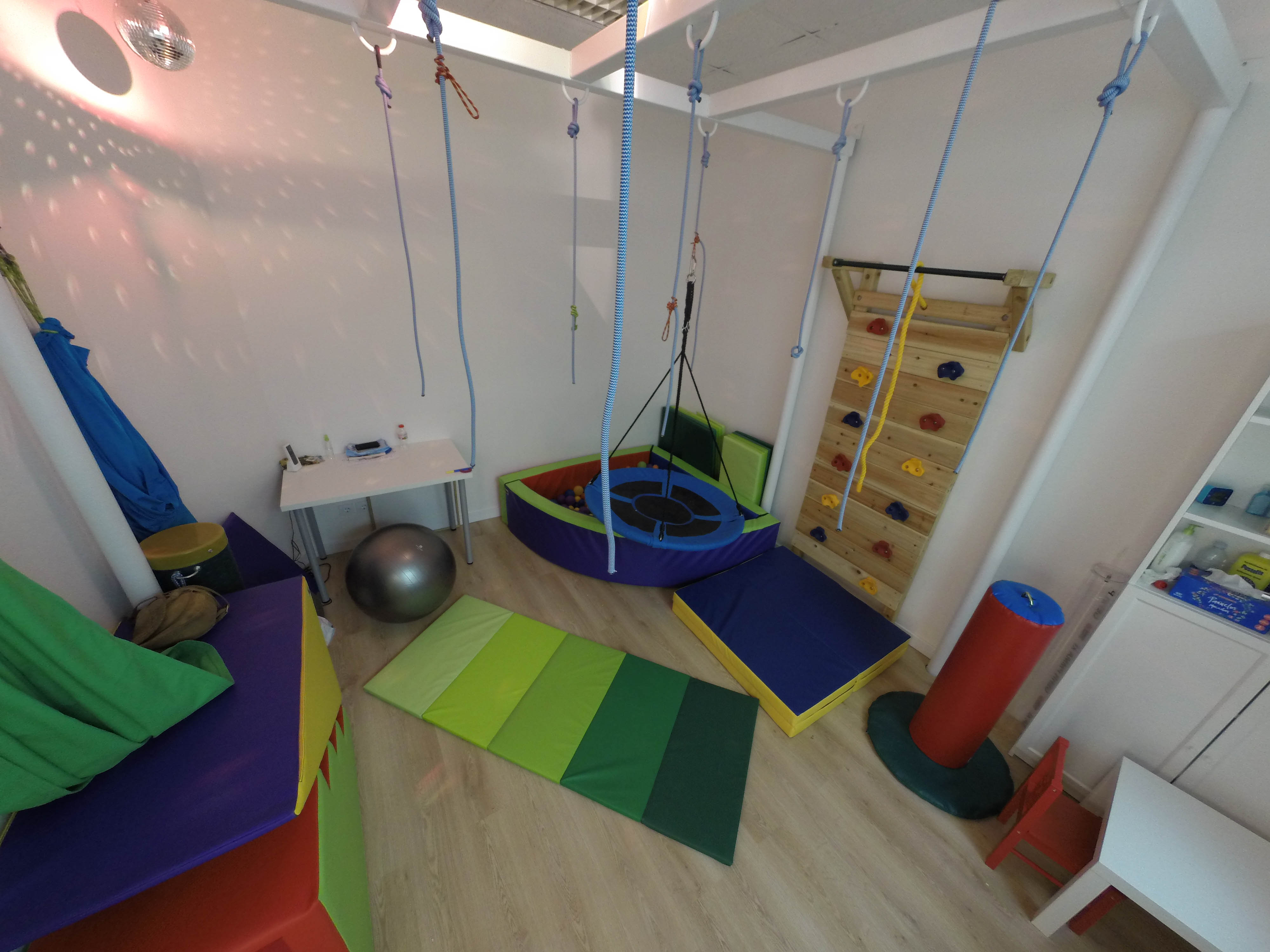Otra Sala del Centro de Integración Sensorial en Valencia, podemos ver colchonetas, rampas, rocódromo, piscina de bolas, pelota enorme y una red de lianas de las que colgarse