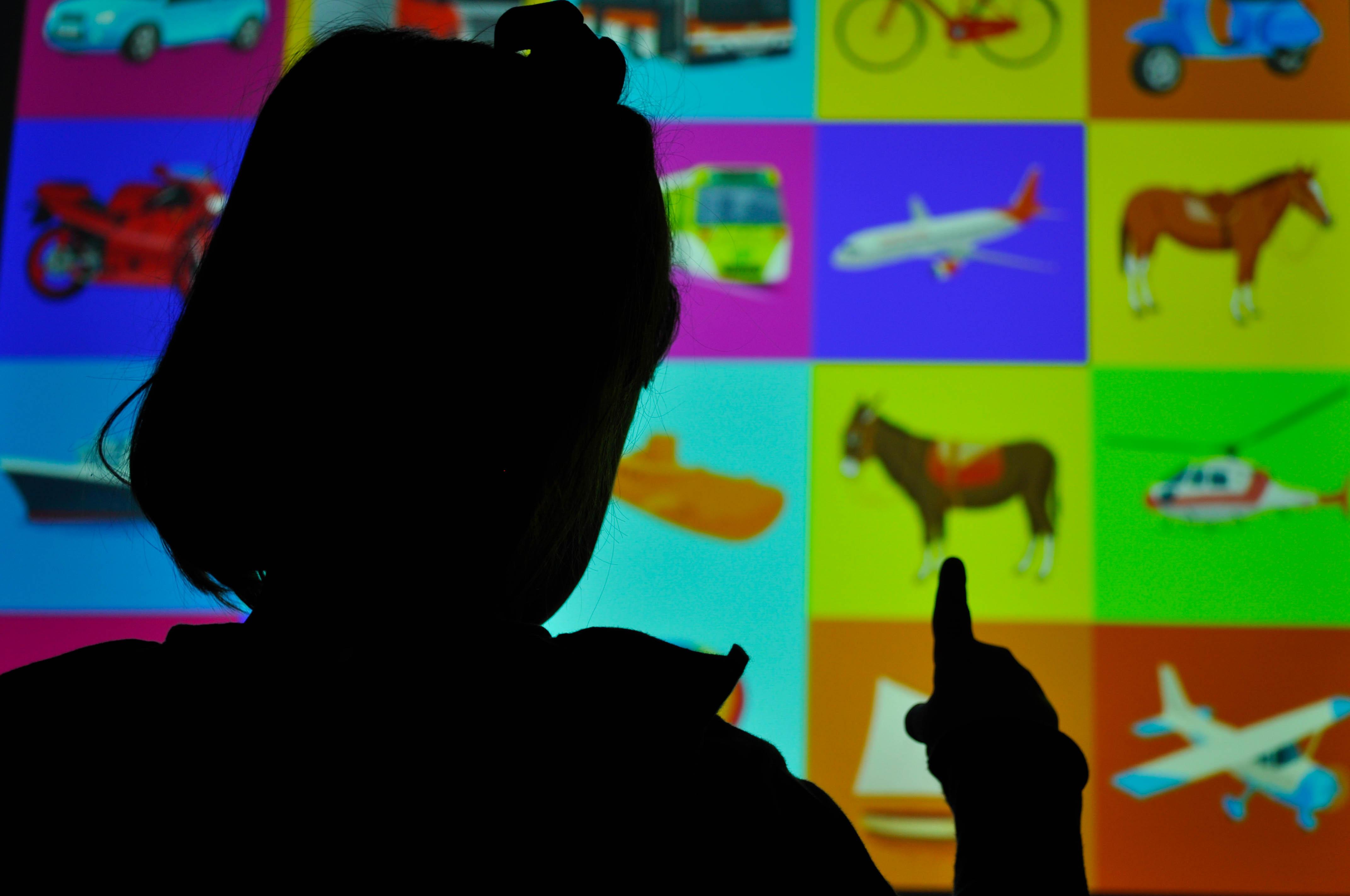 Niña(al trasluz) señalando un póster con diferentes figuras (método de estimulación visual)