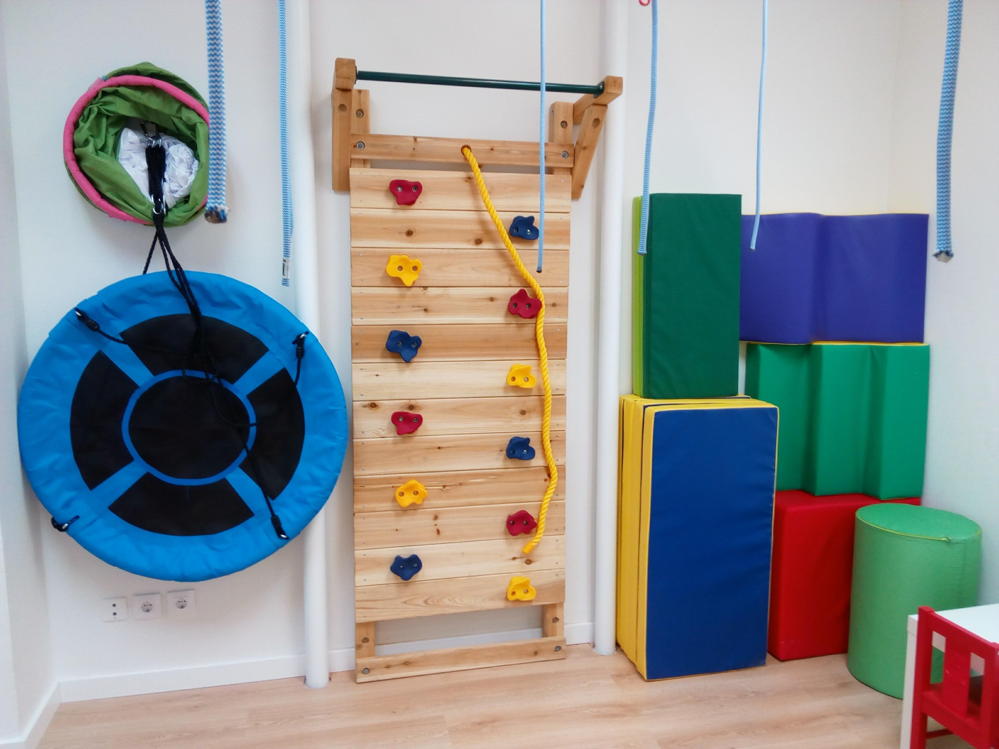 Equipamiento de una de las salas con un rocódromo,colchonetas,cojines,columpio y una red de lianas de las que colgarse