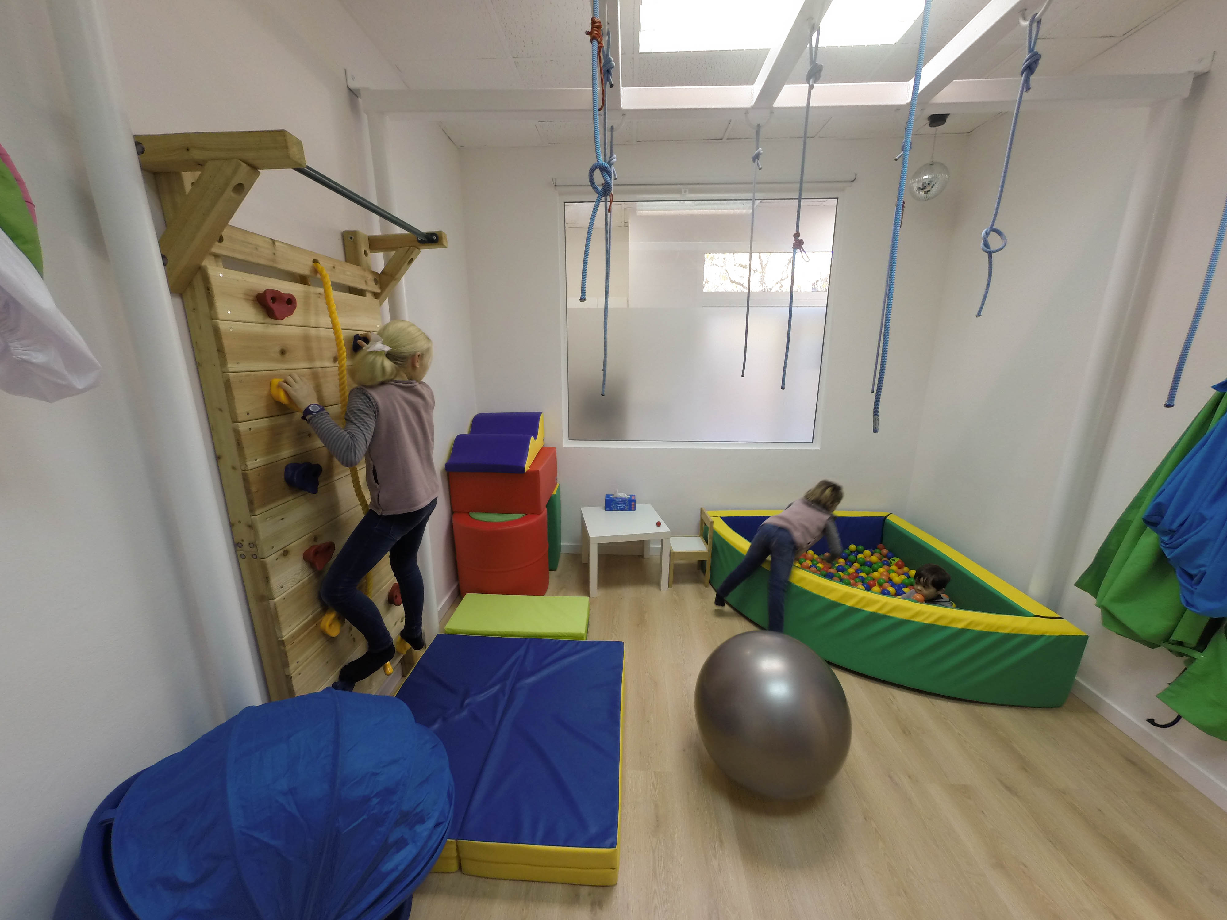 Sala del Centro de Integración Sensorial en Valencia, vemos a una niña subida en un rocódromo, una piscina con bolas, colchonetas,una pelota gigante y una red de lianas de las que colgarse