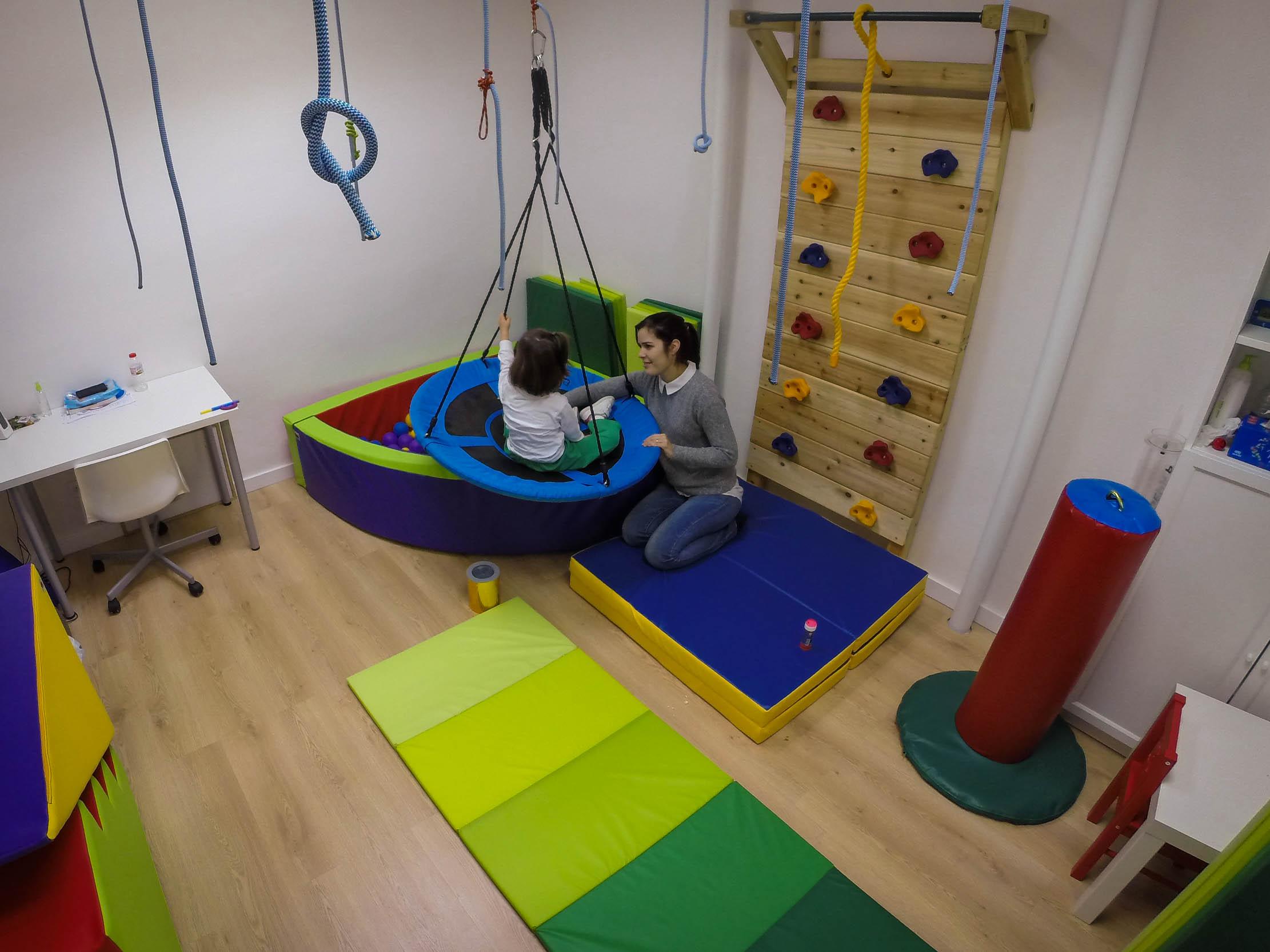 Una de las terapeutas en una sesión cualquiera interactuando con una de nuestras pacientes subida en un columpio