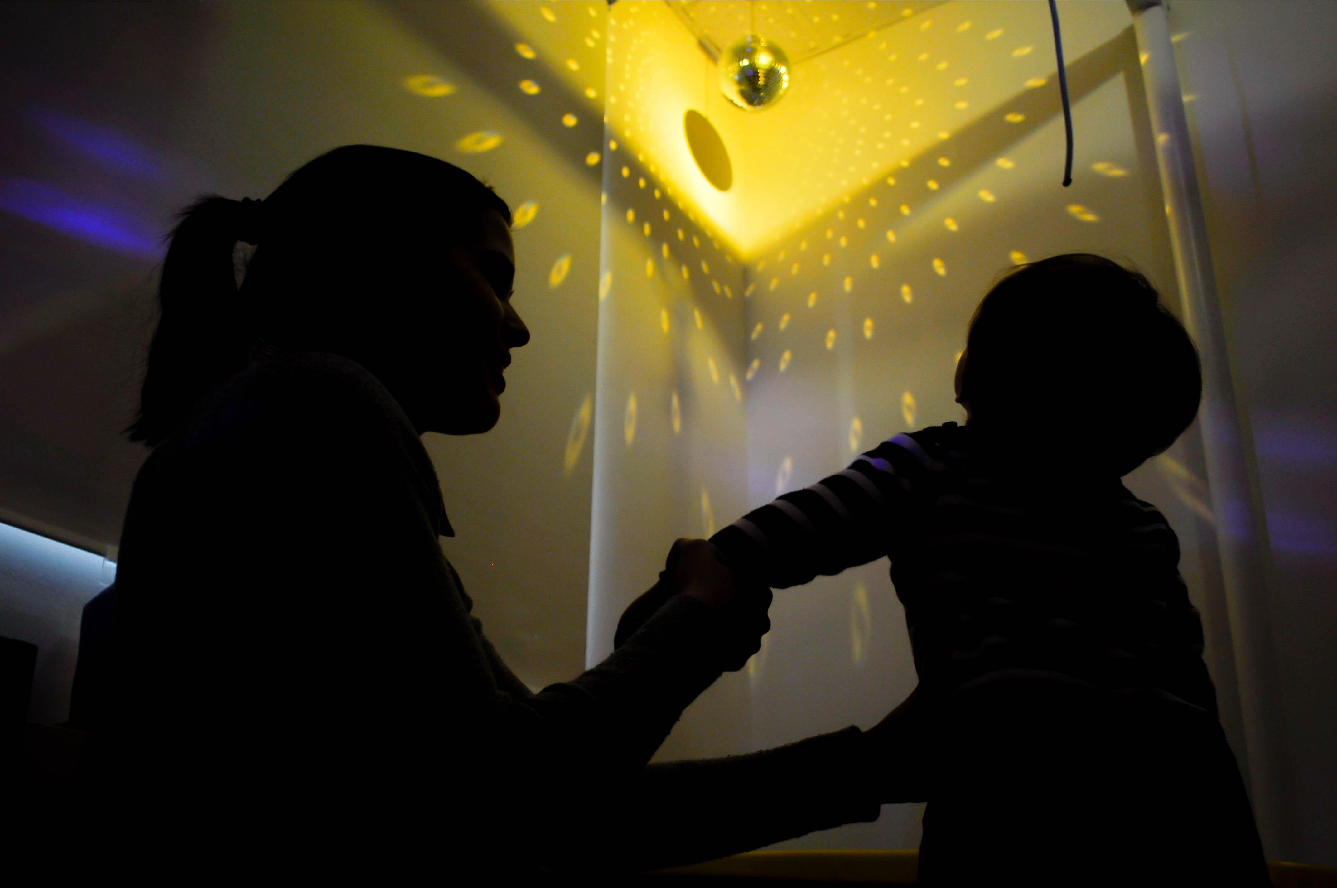 Una terapeuta sostiene a un niño que observa una bola de luz (estimulación visual)