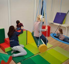Terapeuta en una sesión cualquiera interactuando con un niño en una de las múltiples salas, varias niñas observan con atención